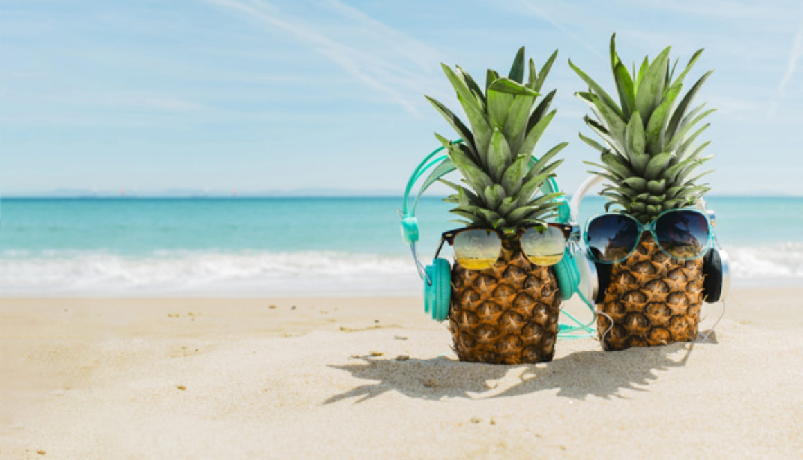 beach-background-with-cool-pineapples-wearing-headphones_23-2147836098
