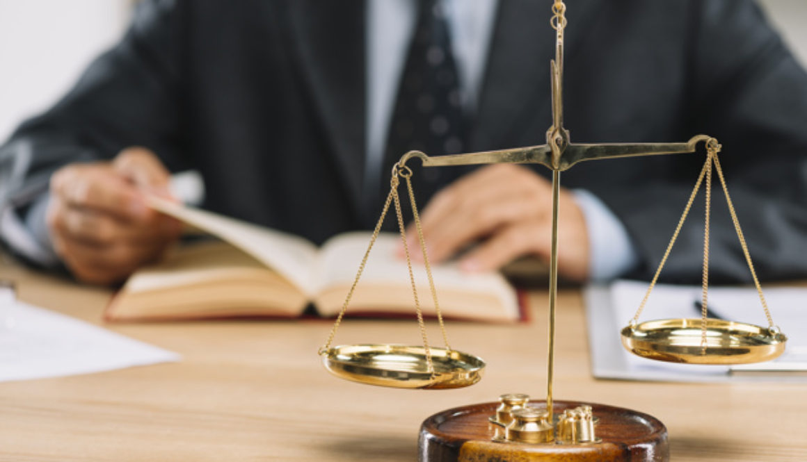 golden-justice-scale-front-lawyer-reading-book-table_23-2147898544